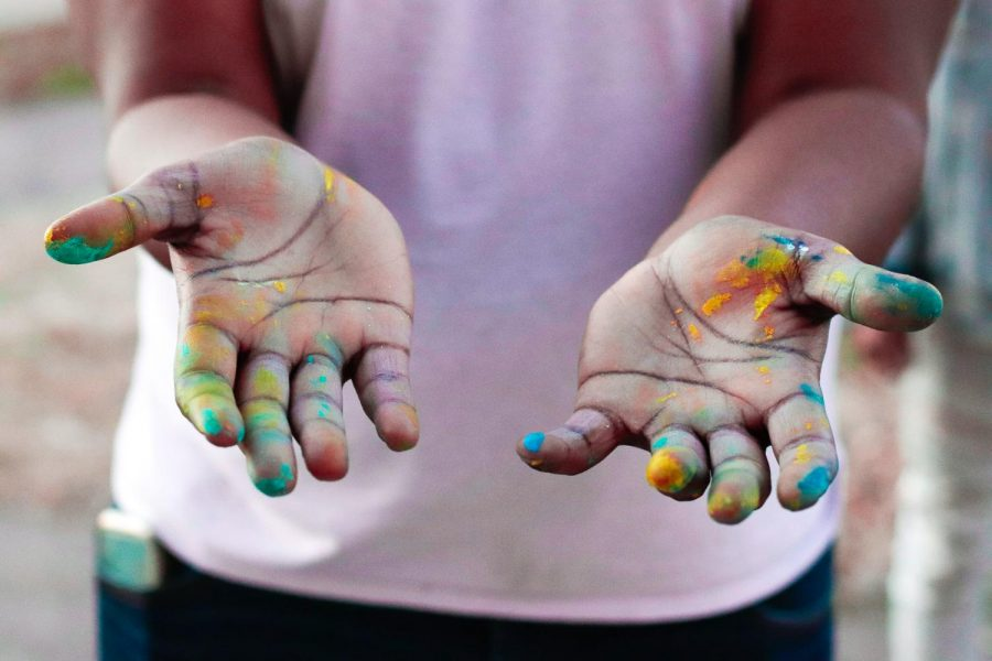 "Artist, Michael Coleman, holds out his paint-covered hands after working on the Art Reconciliation community mural March 5, 2021, in Carbondale, Ill. ""[The mural] talks about the racial unity and we really do need it in southern Illinois. We've had a lot of issues with racism [...] I want to be able to give something for the community for not even just a short period of time, but for a long period of time so more generations can be inspired by it,"" Coleman said."