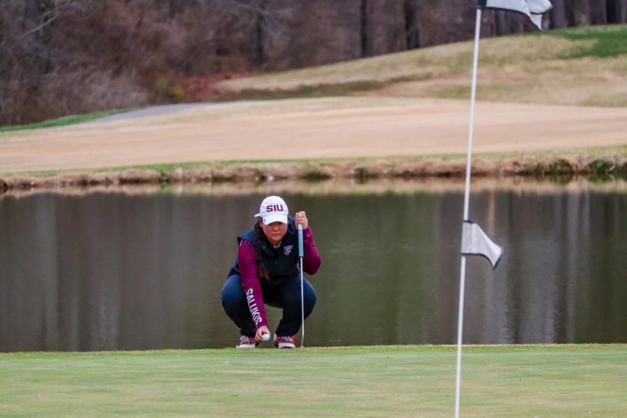 SIU senior, Moyea Russell, evaluates the green during the match against Bradley University March 14, 2021, at Hickory Ridge Golf Course in Carbondale, Ill.