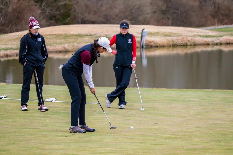 Hollie James putts the ball into the hole during the match against Bradley University March 14, 2021, at Hickory Ridge Golf Course in Carbondale, Ill.