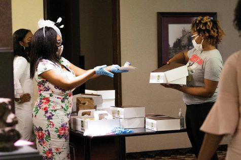 Avian Wilkins distributes lunch to the participants on Wednesday, March 17, 2021 at the Student Center ballroom in Carbondale, Ill.