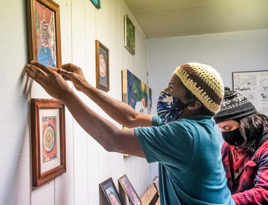 Roosevelt Clerks, a staff member at the Center for Empowerment and Justice, fixes a piece of art on the wall for exhibition on Thursday, Mar. 11, 2021 in Carbondale, Ill.