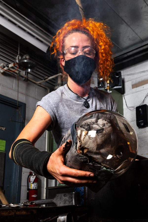 """Sadhbh Mowlds, a second year MFA student from Ireland, works in the glass blowing hot shop at SIU in Carbondale, Ill. Feb. 12, 2021. Mowlds said that she had a rough summer in regard to travelling during the COVID-19 pandemic. She said was able to get into Ireland because she has citizenship there, but had trouble getting into Germany. """"When the borders went down, I was able to get into Germany to see my friends,"""" Mowlds said."""