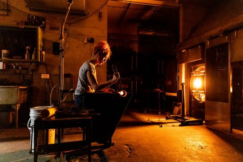 """Sadhbh Mowlds, a second year MFA student from Ireland, works in the glass blowing hot shop at SIU in Carbondale, Ill. Feb. 12, 2021. """"It was really last minute that I decided to get a master's. I was just feeling like I was in a rut and North America has the best reputation for glass schools,"""" Mowlds said."""