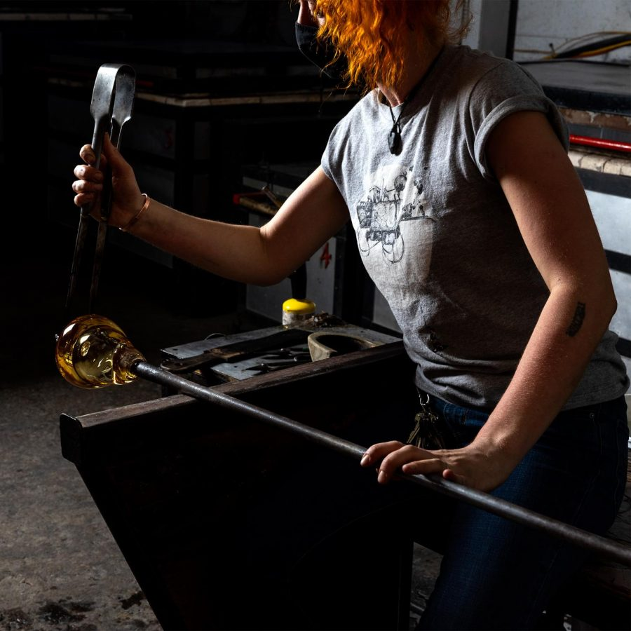 Sadhbh Mowlds, a second year MFA student from Ireland, uses a jack in the glass blowing hot shop at SIU in Carbondale, Ill. Feb. 12, 2021. Jacks can be used to separates the blowpipe from the molten glass.