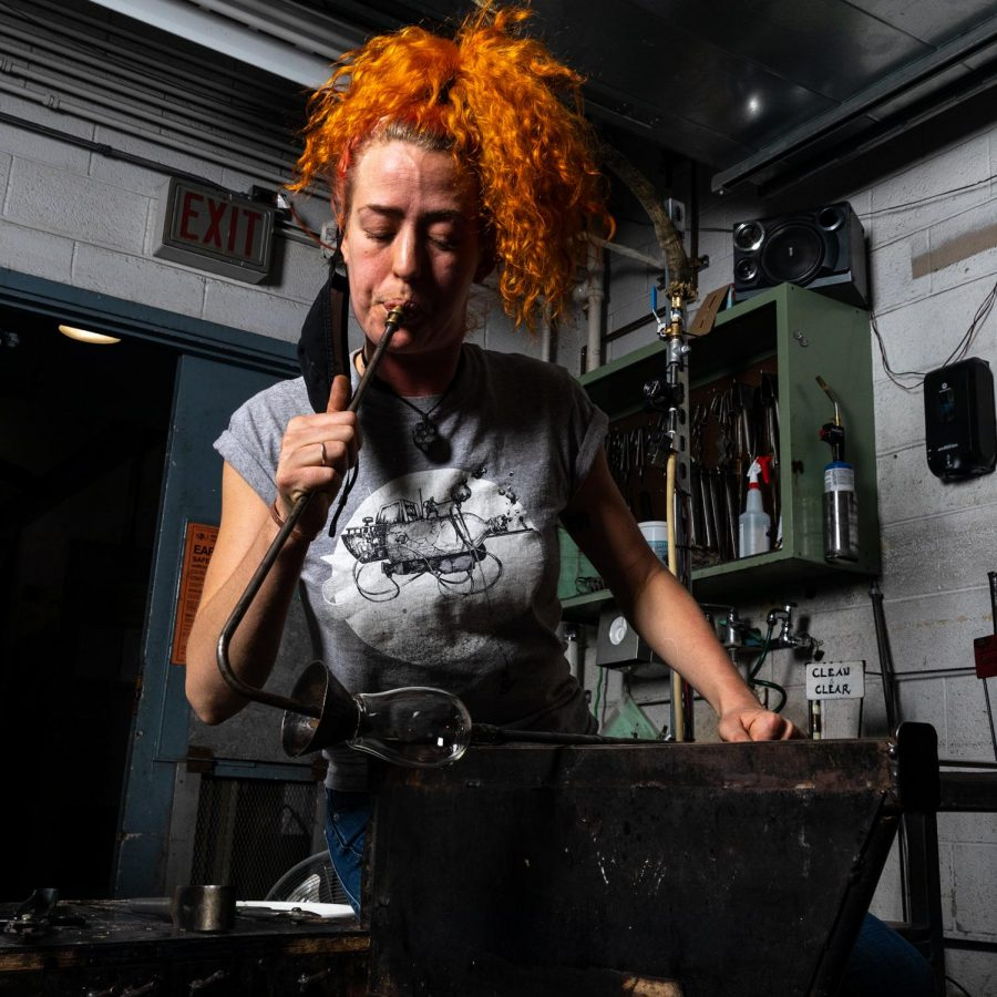 Sadhbh Mowlds, a second year MFA student from Ireland, blows into a blow pipe in the glass blowing hot shop at SIU in Carbondale, Ill. Feb. 12, 2021.