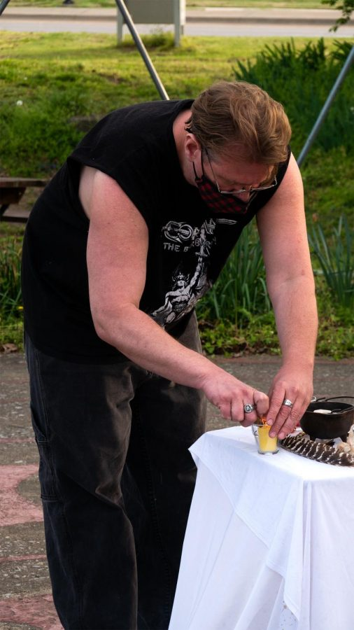 Southern Illinois Pagan Alliance member, Brandon Hale, lights candles on an altar just before the start of a ritual smudging Wednesday, April 14, 2021, in Carbondale, Ill.