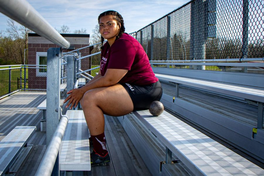 SIU thrower A'veun Moore-Jones sits for a portrait with a shot put on Tuesday, April 6, 2021 at Lew Hartzog Track & Field Complex at SIU. Moore-Jones was named All-MVC for a second time in her career and went on to take home first place in shot put at Missouri Valley Conference championship. After finishing 14th place in shot put at the NCAA Indoor Championships, she was named to the 2021 Second Team All-American status.