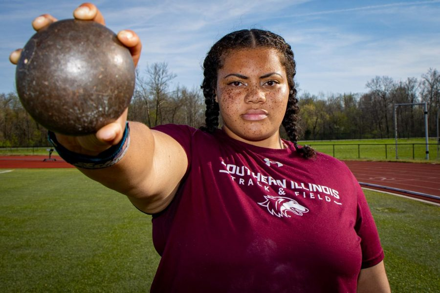SIU thrower A'veun Moore-Jones poses with a shot put on Tuesday, April 6, 2021 at Lew Hartzog Track & Field Complex at SIU. Moore-Jones was named All-MVC for a second time in her career and went on to take home first place in shot put at Missouri Valley Conference championship. After finishing 14th place in shot put at the NCAA Indoor Championships, she was named to the 2021 Second Team All-American status.