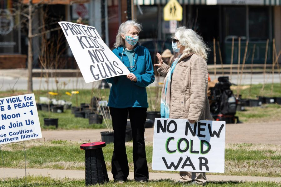 Protestors hold their signs during the Peace Coalition of Southern Illinois' community rally for peace and justice on Saturday, April 3, 2021 on the corner of Main Street in Carbondale, Ill.