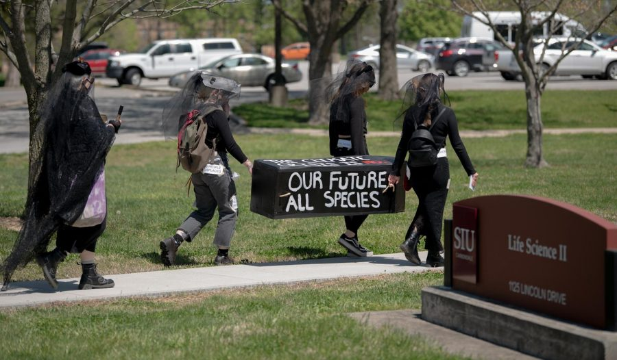 SIU students participate in a funeral casket walking honor of countless species of animals that have gone extinct on Thursday, April 22, 2021. The walk started at the SIU Communications Building to the student center. Students wore all  black outfits in mourning with some messages about the climate change crisis on them.