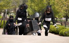 SIU students towards the SIU Morris Library in a funeral casket walking honor of countless species of animals that have gone extinct on Thursday, April 22, 2021.