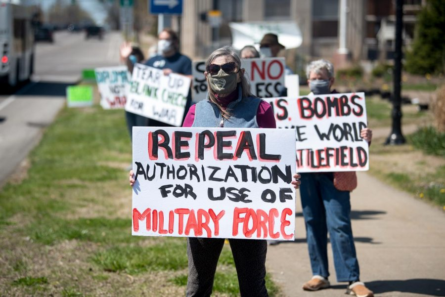 "Corina Lang holds a sign in protest during the Peace Coalition of Southern Illinois' community rally for peace and justice on Saturday, April 3, 2021, on the corner of Main Street in Carbondale, Ill. "" We support our country and don't want young people to be in unnecessary wars,"" Lang said."