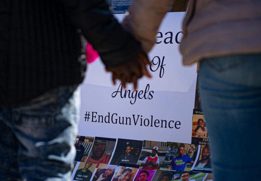 Two people hold hands as they gaze at a banner with images of people who have lost their lives to gun violence on Friday, April 2, 2021 in Decatur, Ill.