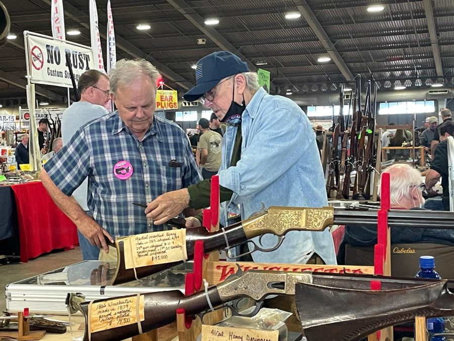 Two gun sellers inspect a revolver at the world's largest gun show, the Wanenmacher's Tulsa Arms Show. The show was a two day event and took place on April, 10 and 11, 2021, at Expo Square in Tulsa, Okla. More than 25,000 people participated in  the show.