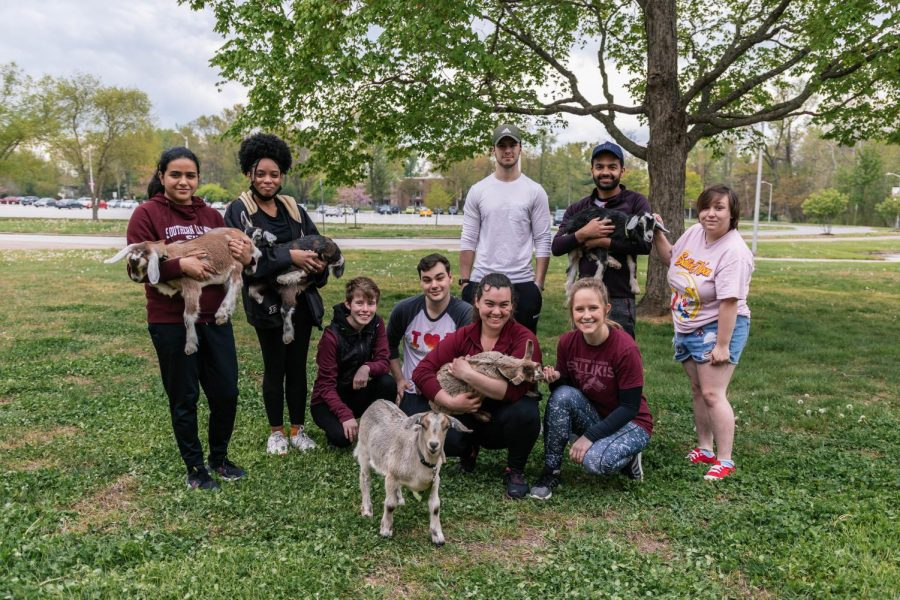 Some of the Daily Egyptian staff pose with the goats during goat yoga on April 17, 2021 in Carbondale, Ill.