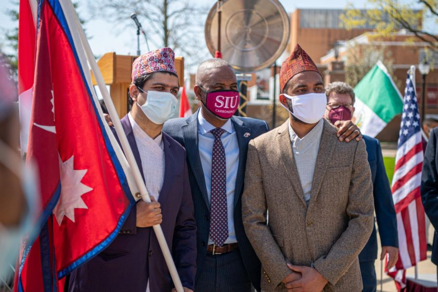 A couple of students pose for a photo with SIU chancellor Austin Lane, after the International Festival Proclamation Monday, April 5, 2021 at Faner Plaza at SIU.