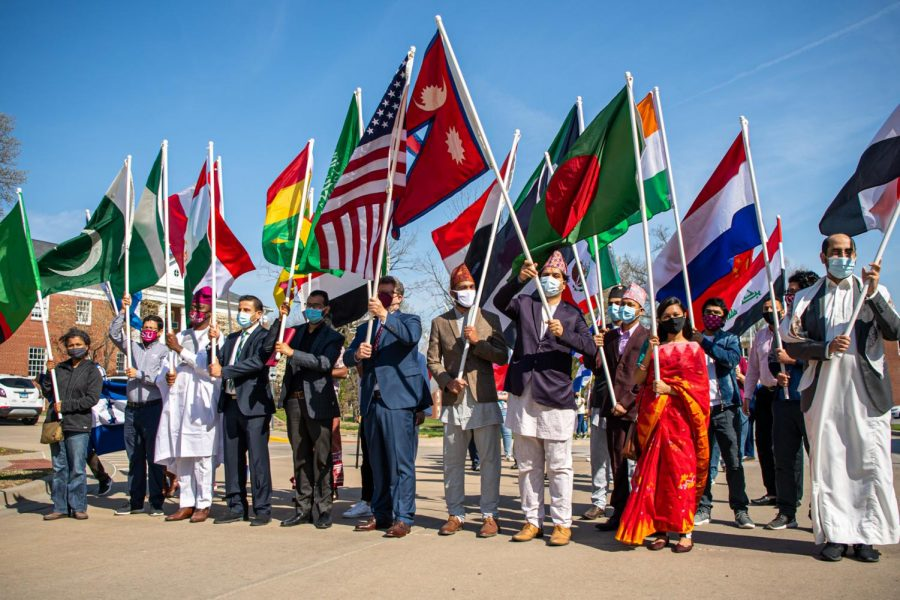 Parade participates fly their flags in the air during the International Parade of Flags Monday, April 5, 2021 at SIU. The parade is the kick-off event apart of the International Fest 2021, a week long celebration for international students at SIU.