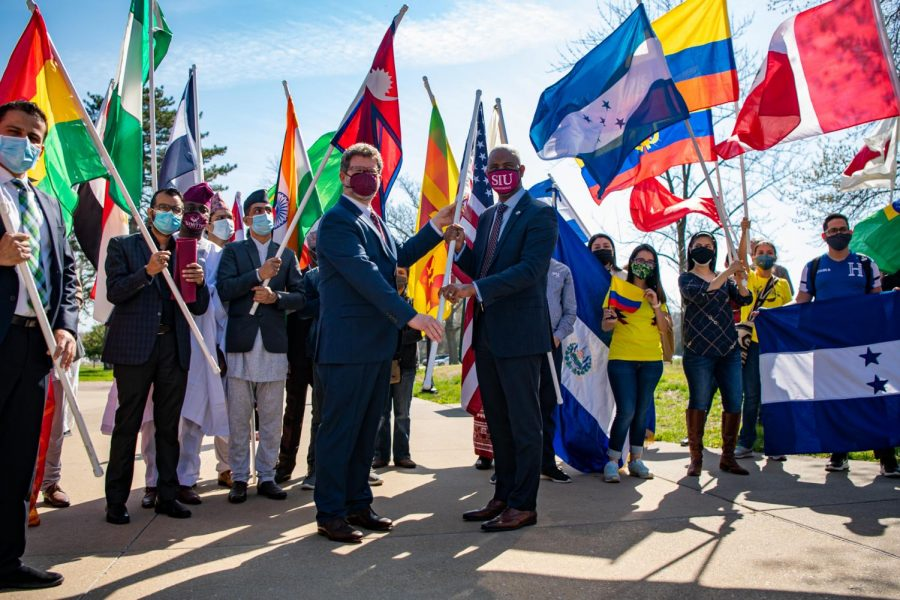 Executive Director of International Affairs Andrew Carver, heads off a flag to Austin Lane, SIU chancellor, during the International Parade of Flags Monday, April 5, 2021 outside Anthony Hall at SIU.