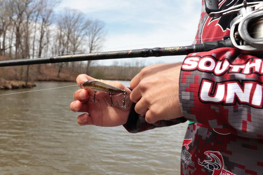 Thomas (TJ) Johns holds a fishing lure March 31, 2021, at Kinkaid Lake in Jackson County, Ill. Johns said that the fishing club is a registered student organization and they travel all over the country to fish in tournaments.