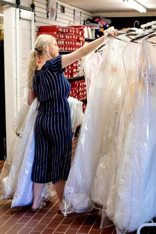 Taylor Hoffman organizes dresses at Melise's Boutique April 3, 2021, in Marion, Ill.