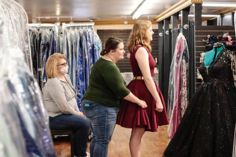 "Nicole Miskelley helps fit a client for a dress April 3, 2021, at Melise's Boutique in Marion, Ill. Miskelley entered into the formal wear business in 2019 and said it was difficult to begin her business during the pandemic. ""We were shut down March of last year up until about October [...] so it's been really hard, especially it being my first year in business, trying to get everything going,"" Miskelley said."