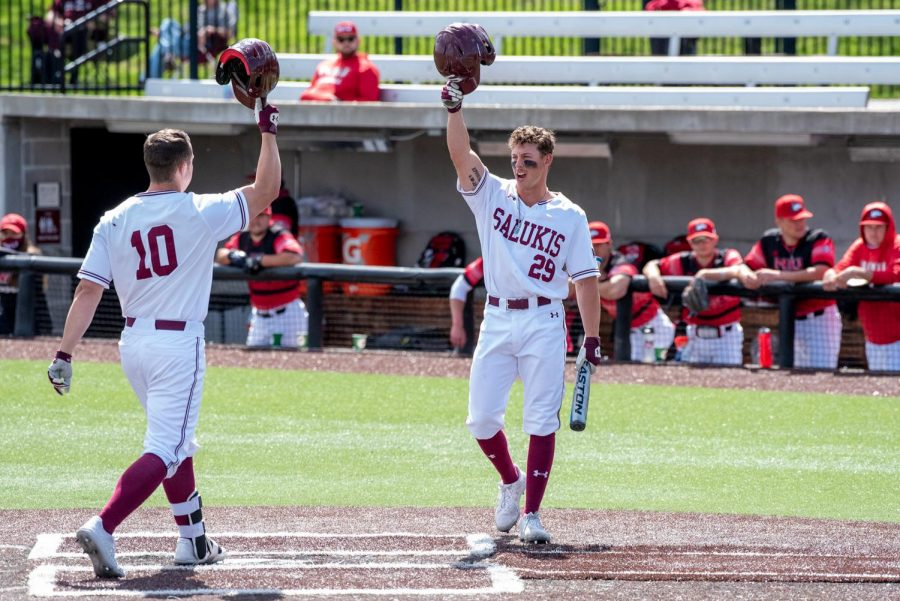 SIU players, Vinni Massaglia (10) and Cody Cleveland (29), congratulate each other after Massaglia hits a home run in the third inning during the game against NIU on Saturday April 10, 2021 at Itchy Jones Stadium in Carbondale, Ill.