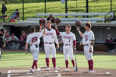 Saluki players Phillip Archer (44) Brad Hudson (4) and Tony Rask (18) congratulate Cody Cleveland (29) after hitting a home run in the second inning during the game against Bellmore on April 10, 2021 at Itchy Jones Stadium in Carbondale, Ill.