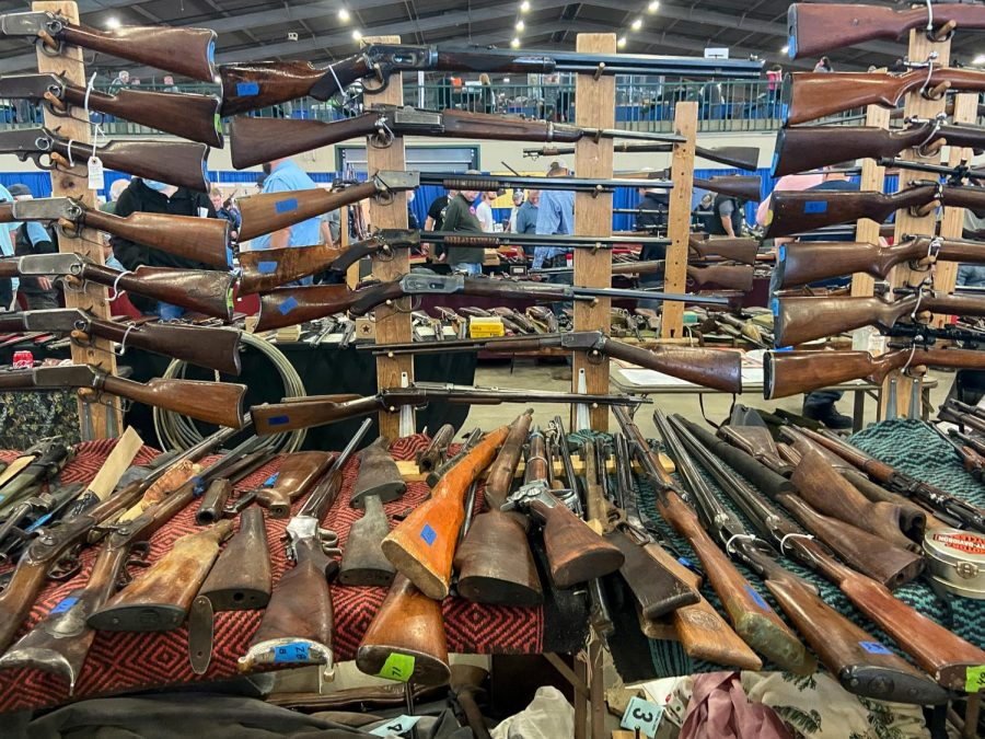 Guns pile up on the tables at the Wanenmachers Arms Show April 10, 2021 in Tulsa, Okla. The gun show is the largest gun show in the world and has been held for over sixty years.