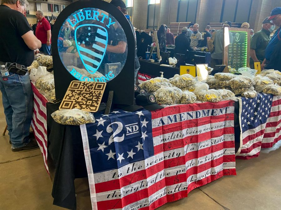 The Liberty Reloading sign sits beside a second amendment flag at the Wanenmachers Arms Show April 10, 2021 in Tulsa, Okla. The company sells rifle casings and uses once-fired brass from indoor shooting ranges.
