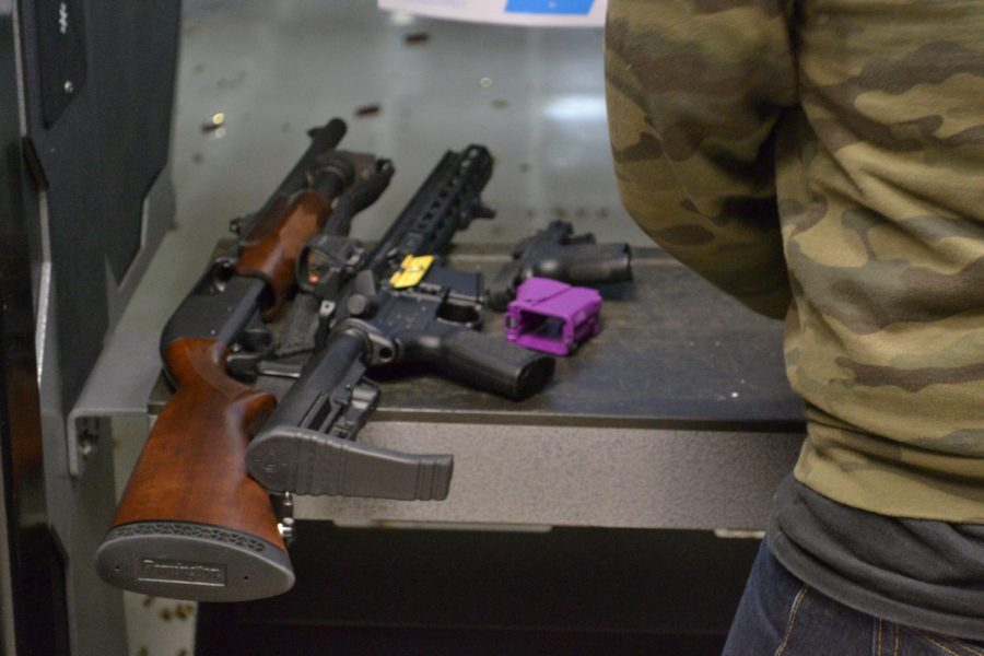 """A shotgun, AR and handgun rest on a podium at a shooting range in Chicago, Ill. suburbs. """"There's no reason why I can't take this off and put it on a pistol AR,"""" Seth said, pointing to the butt of the rifle. """"Well, there is a reason. It's because it's a felony."""""""