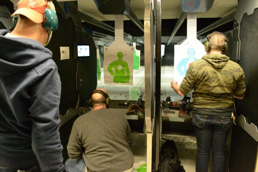 A spectator looks on as Jack B. and Seth M. loaded guns at a shooting range in the Chicago, Ill. suburbs.