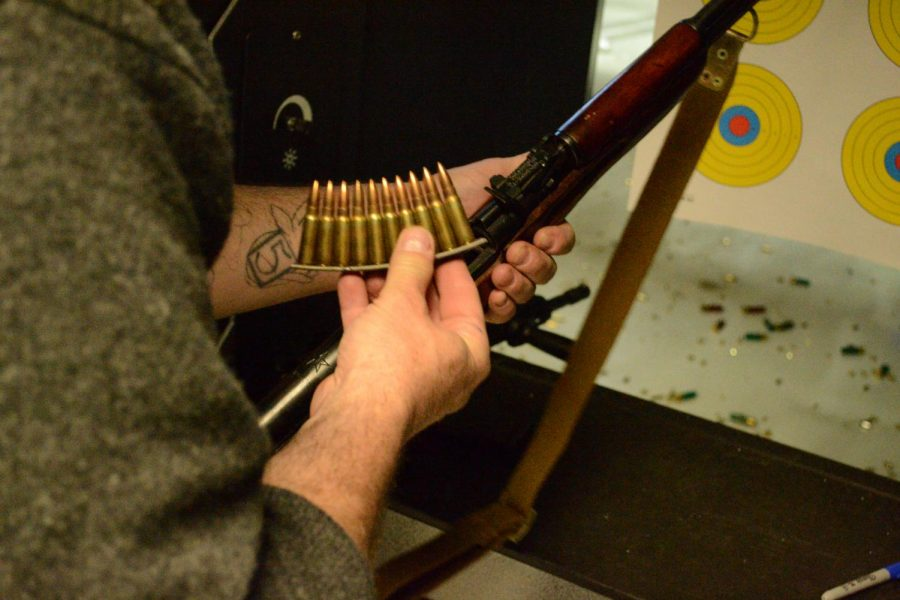 Jack B. whose name has been changed for the condition of anonymity, held a stripper clip before loading an SKS rifle at a shooting range in the Chicago, Ill. suburbs.