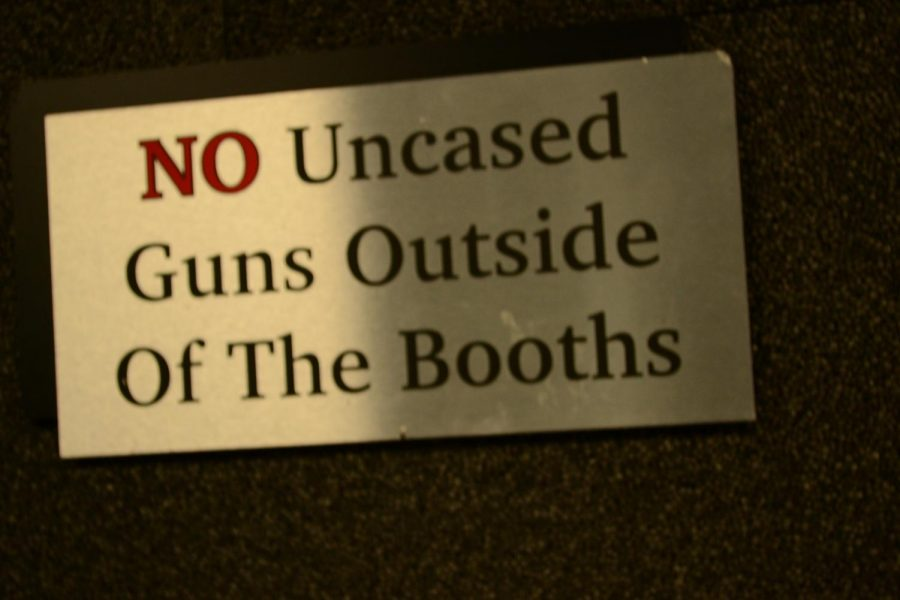 """A sign reads """"No Uncased Guns Outside Of The Booths"""" at a shooting range in the Chicago suburbs."""