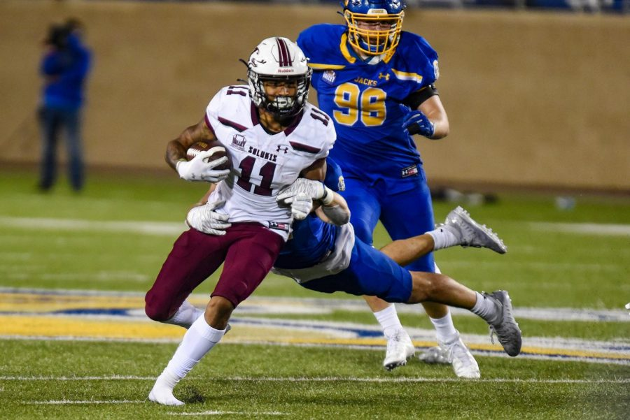 Avante Cox (11) runs with the ball  in the game against South Dakota State on Sunday, May 2, 2021 in Brookings, S.D. SIU went on to lose 26-31 against the Jackrabbits.