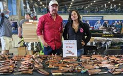 Brandon Kuschnereit and Hollie Andress stand behind their table of hand-crafted knives at the Wanenmachers Arms Show April 10, 2021 in Tulsa, Okla. Many booths participated in the show with products ranging from a small knife to military grade rifles.