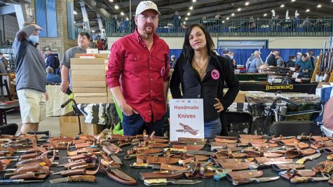 Brandon Kuschnereit and Hollie Andress stand behind their table of hand-crafted knives at the Wanenmacher