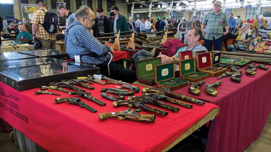 """A group of sellers sit in their booth with their antique collections at the Wanenmacher's Arms Show April 11, 2021 in Tulsa, Okla. """"My first visit to the gun show was somewhere in the 1960s and my first in Oklahoma was in 1989,"""" one said. The history that weapons carry lured them to trading the guns."""