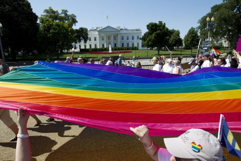 Demonstrators hold up a rainbow flag as they march outside of the White House during the Equality March for Unity & Pride parade in Washington D.C., June 11, 2017.