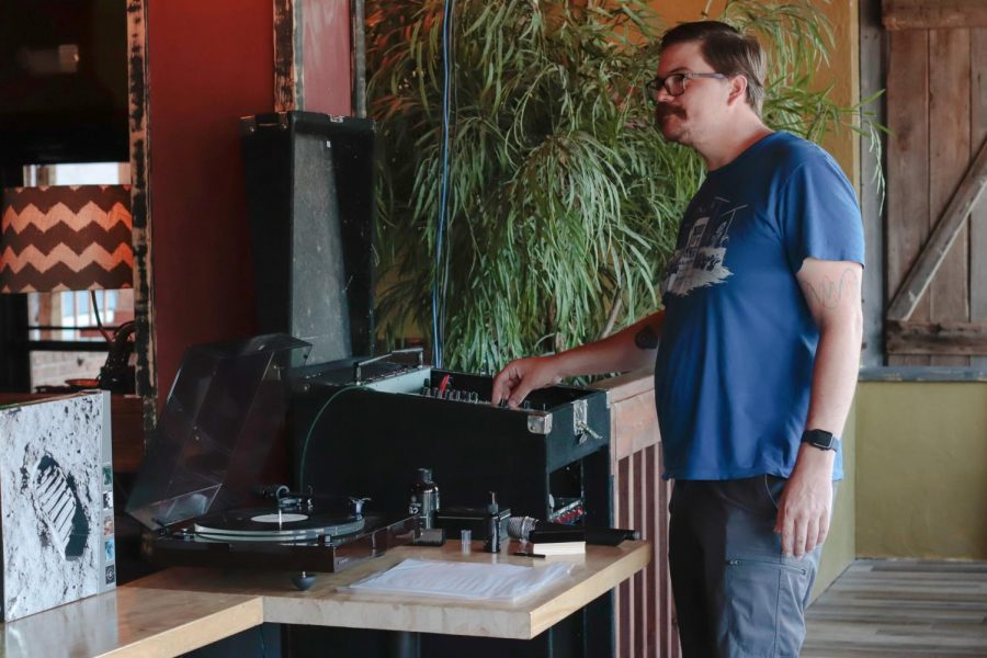 """Josh Combs plays a vinyl record over the house speakers Aug. 11, 2021 at the Record Swaps and Needle Drops event at Buckwater Brew Works and Whiskey House in Carbondale, Ill. Combs organized the event and said, """"It's something that kind of came out of just listening to records with friends and thinking that enough people enjoy listening to records that they might come out and like to do it in public."""""""