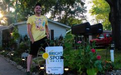 """Rick Crossley stands in front of his yard beside his Bright Spot award from Keep Carbondale Beautiful Aug. 12, 2021 in Carbondale, Ill. . Since winning the award, he has witnessed an increase in members of the community stopping by and connecting with each other. """"It touches my heart when people I know did not have any interactions come and I see them walking by together in the mornings. It's really touching, """" Crossley said."""