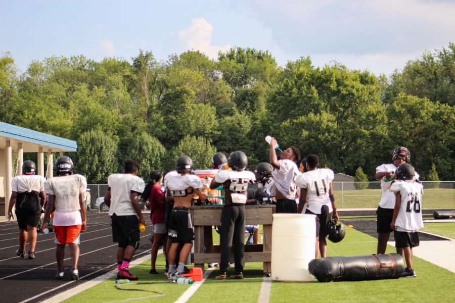 """Carbondale High School Terrier football team takes a water break during practice Aug. 19, 2021, in Carbondale, Ill. The students have been working hard in hopes for a smooth season. Coach Bryan Lee said, """"We just survived this crazy spring of football right at the edge of winter. Theoretically, right now, perfect world, fingers crossed, that the athletic schedule here will look normal. Kids are in the building, we're playing a normal schedule."""""""