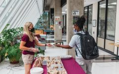Savannah Long hands out bagels on Bagel Wednesday Aug. 18, 2021 at Faner Hall.