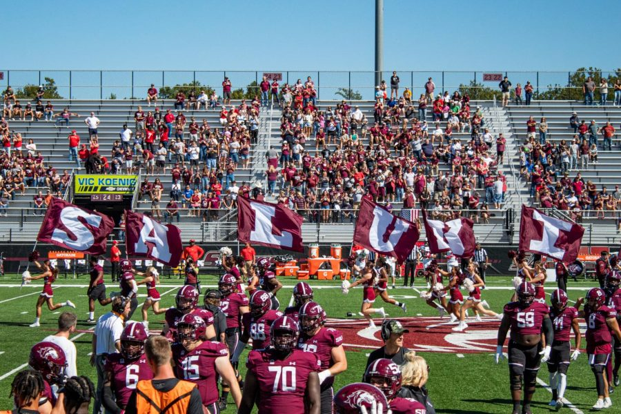 """SIU cheerleaders run across the field holding flags that spell """"SALUKIS during the beginning of the game against Illinois State University Sept. 25, 2021 at the Saluki Stadium in Carbondale, Ill."""