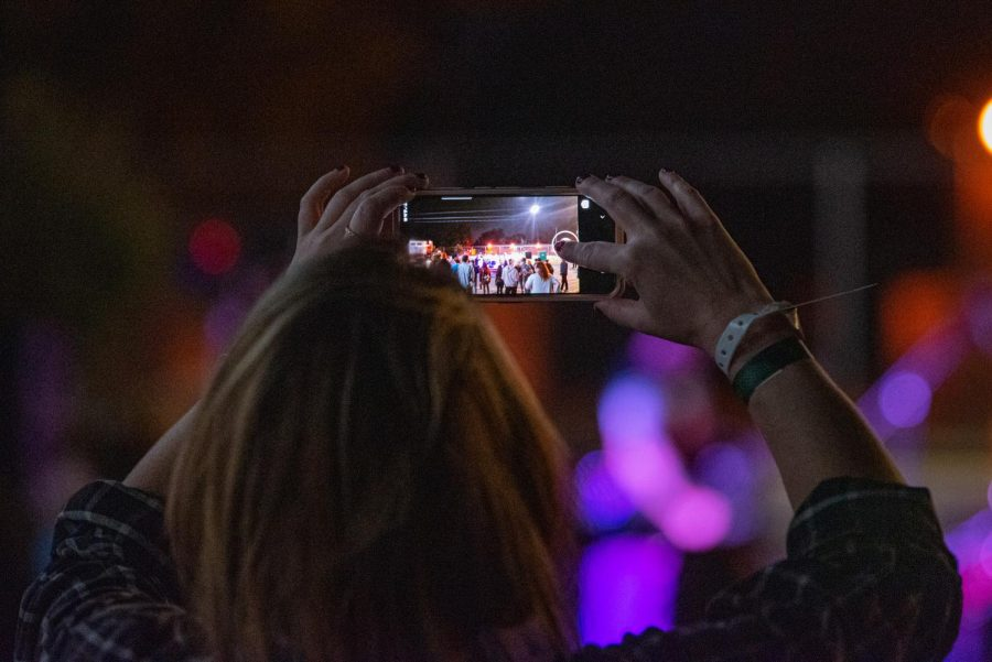 A concertgoer holds their phone up for a photo of a performance outside Hanger 9 during the Lost Cross 35th anniversary event. The Lost Cross House, the oldest punk house venue in America, that sits between Elm and Beveridge was founded by Mikey Snot and Chris Cross in 1986. Lost Cross 35th anniversary was a two-day event that had musical performances at venues across the city on Friday, Sept. 24, 2021 in Carbondale, Illinois.