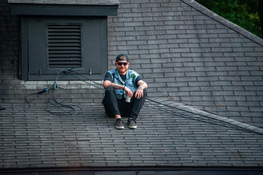 A concertgoer sits on the roof of The Lost Cross House while waiting for the next band to go on during the Lost Cross 35th anniversary event. The Lost Cross House, the oldest punk house venue in America, that sits between Elm and Beveridge was founded by Mikey Snot and Chris Cross in 1986. Lost Cross 35th anniversary was a two-day event that had musical performances at venues across the city on Saturday , Sept. 25, 2021 in Carbondale, Illinois.