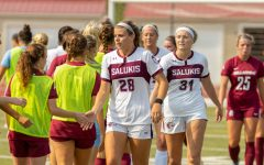 SIUs McKensey Bunch, left, and Paris Walsh, right, high five members of the Bellarmine soccer team after the Salukis game against Bellarmine University, where the Knights won 2-0 against the Salukis on Sunday, Sept. 12, 2021 at Lew Hartzog Track and Field Complex at SIU.
