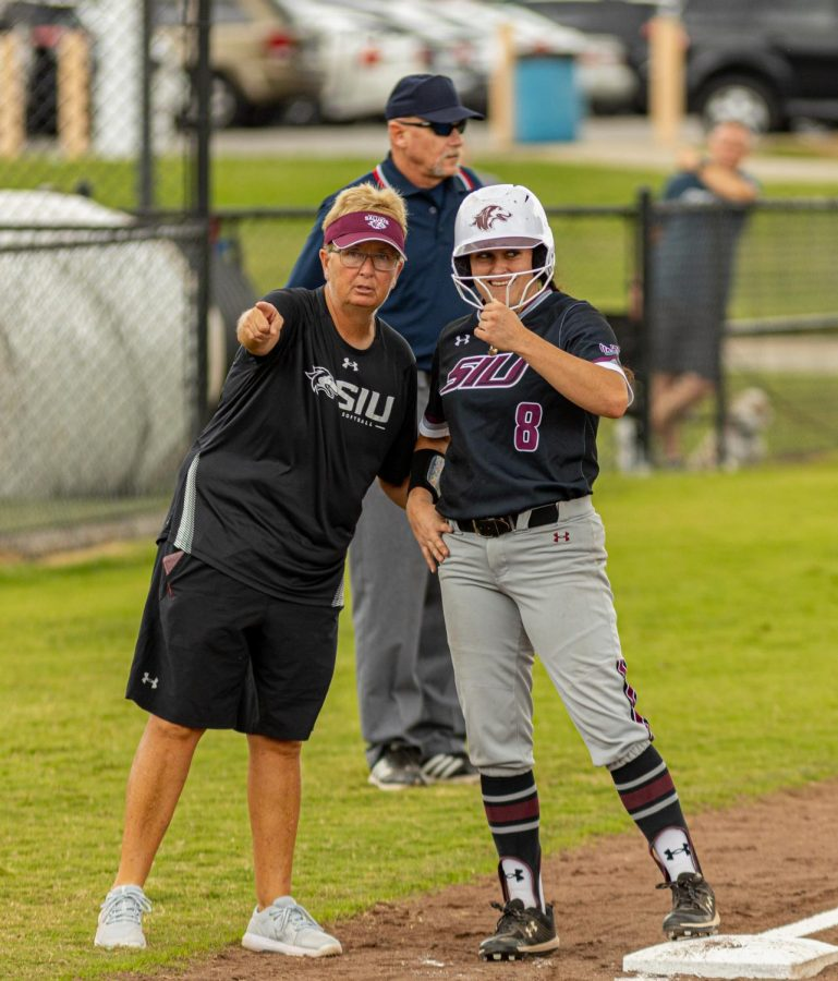 SIU head coach Kerri Blaylock, left, talks to SIU baserunner Elizabeth Warwick after she gets on base after a base clearing triple during the second game of the doubleheader vs. Three River Community College. The Salukis would win both games on Sunday, Sept. 19, 2021 at the Charlotte West Stadium in Carbondale, Illinois.