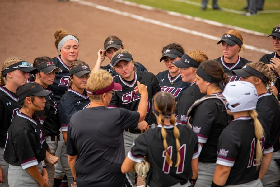SIU softball gathers for an between inning talk from head coach Kerri Blaylock during the first game of the doubleheader vs. Three River Community College. The Salukis would win both games on Sunday, Sept. 19, 2021 at the Charlotte West Stadium in Carbondale, Illinois.