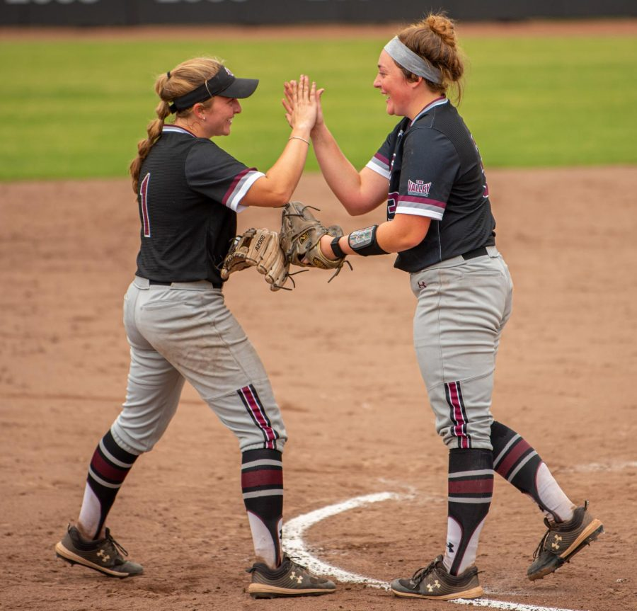 SIU infielder Rylie Hamilton, left, high-fives Madi Eberle after Hamilton caught a line drive ball during the first game of the doubleheader vs. Three River Community College. The Salukis would win both games on Sunday, Sept. 19, 2021 at the Charlotte West Stadium in Carbondale, Illinois.