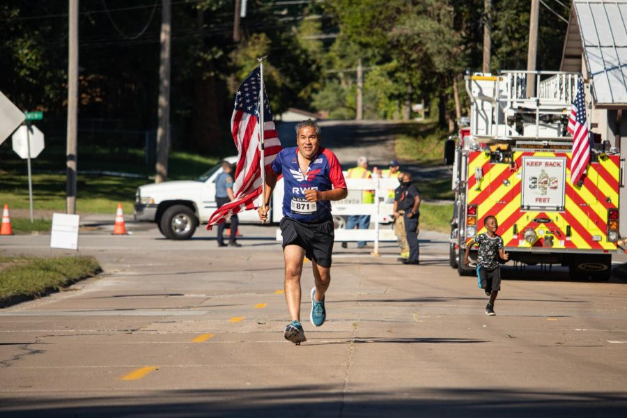 Joe+Gomez%2C+age+55%2C+carries+the+American+flag+as+he+sprints+toward+the+finish+line+of+the+Superhero+5K+Sept.+25%2C+2021+in+Carbondale%2C+Ill.+Gomez+finished+the+race+in+33+minutes+and+46+seconds+as+part+of+team+Red%2C+White+and+Blue.+%5BThe+team+is%5D+an+organization+started+to+create+positive+vibes+through+physical+activity%2C+Gomez+said.+